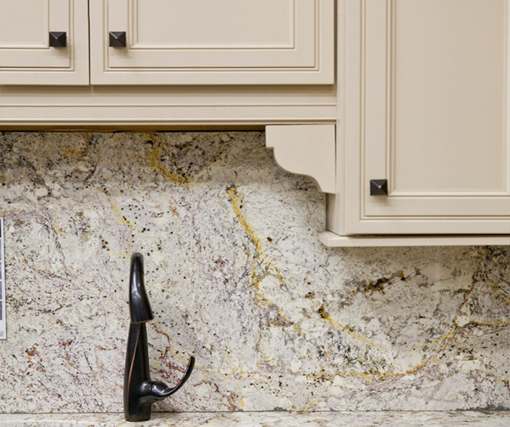 Solid granite kitchen backsplash slab, gray with black and yellow veining.