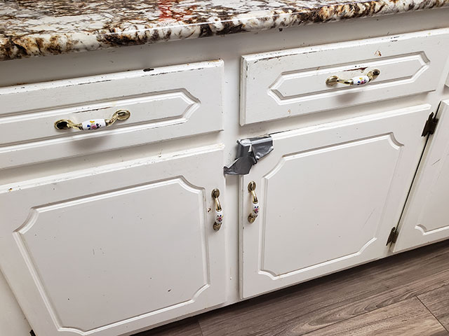 Dated kitchen with broken cabinet held together by duct tape