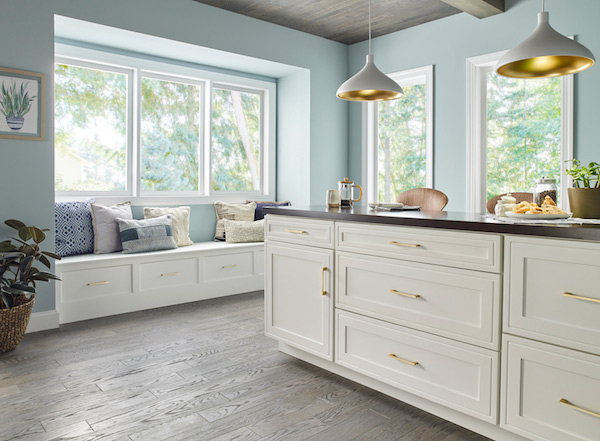 Shaker style white cabinets with gold pull handles and modern lighting.