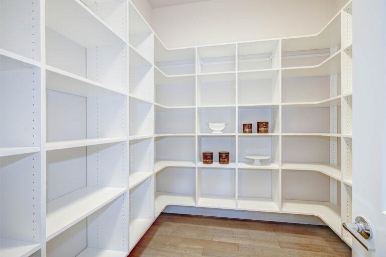 Custom built White pantry interior with wraparound shelves.